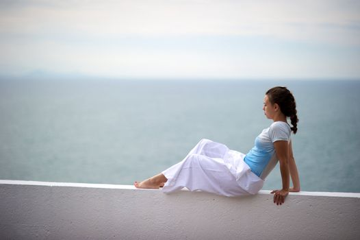 Woman relaxing on a wall in a resort in Porto Belo, Santa Catarina, Brazil