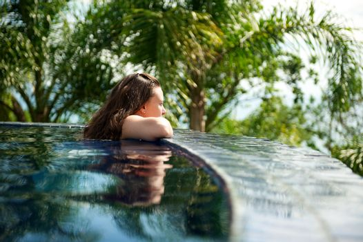 Woman relaxing in a paradise swimming pool in a resort in Porto Belo, Santa Catarina, Brazil