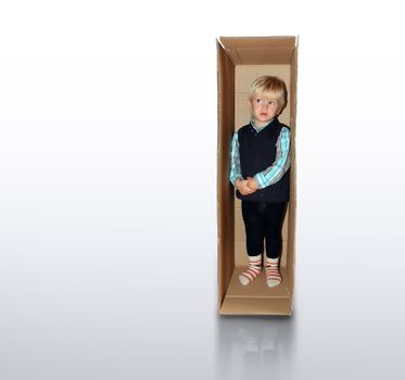 little boy is standing in the brown box alone