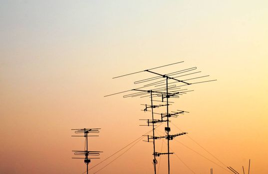 silhouettes of antennas with sunset