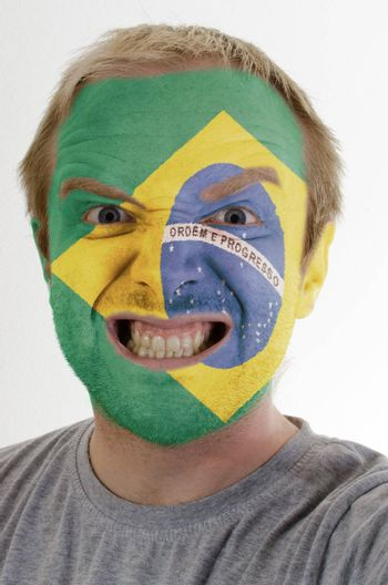High key portrait of an angry man whose face is painted in colors of brazil flag