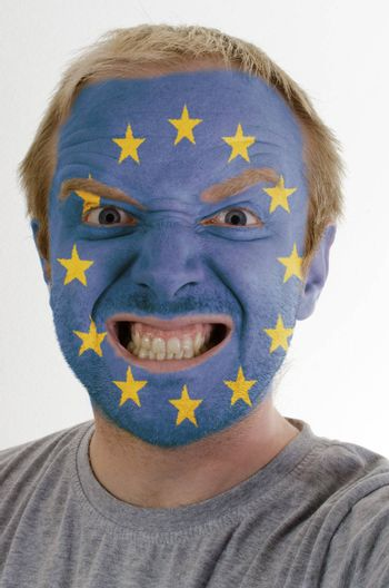 High key portrait of an angry man whose face is painted in colors of europe flag