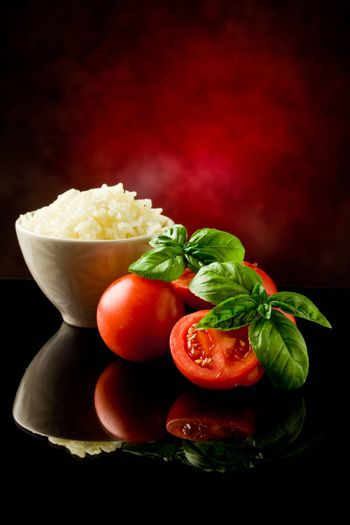 photo of rice inside a bowl with basil and fresh cherry tomatoes