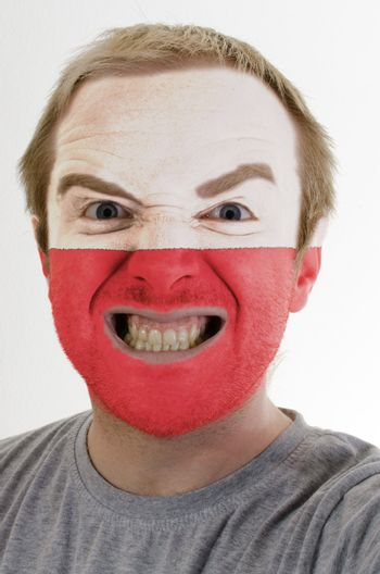 High key portrait of an angry man whose face is painted in colors of polandl flag