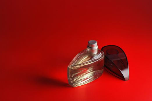 perfume. A bottle perfume on a red background with effective illumination