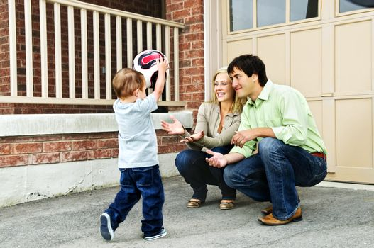 Happy young family playing soccer with toddler on driveway
