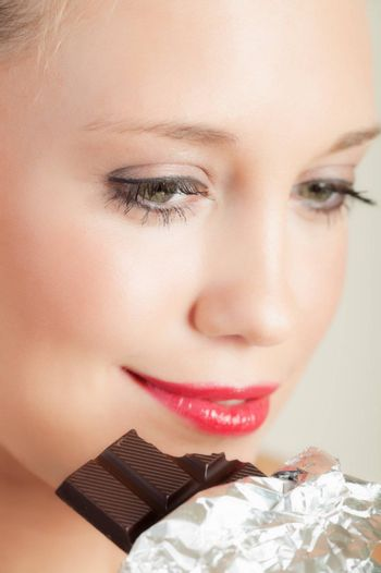 Closeup portrait of a pretty young woman biting chocolate