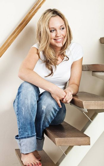 Pretty young smiling woman sitting on steps at home