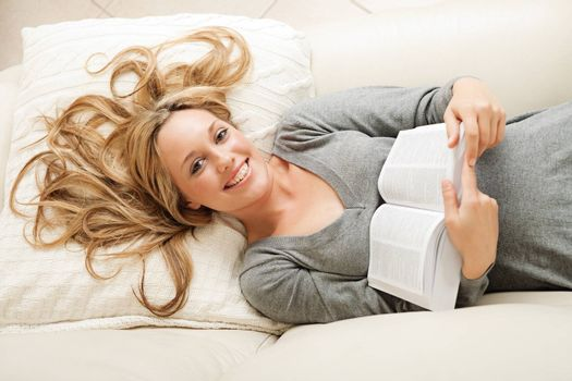 High angle view on smiling blond woman lying on sofa with book