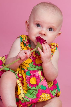 Beautiful baby girl eating flower
