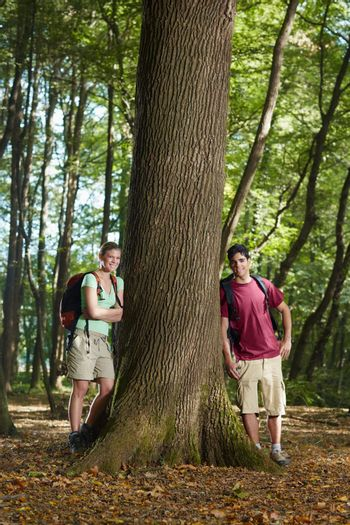 environmental conservation: young hikers leaning on tree