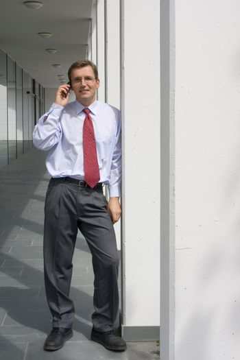 Businessman talking on mobile phone at aa office building