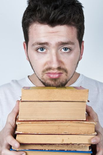 Young man holding a stack of old books looking bored and unhappy