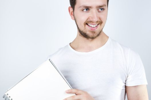 Isolated image of a young blonde man holding a notebook and smiling happily