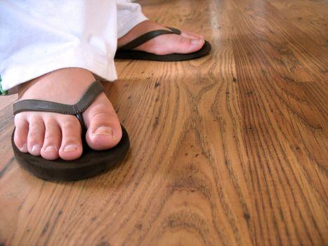 A closeup of a woman's feet wearing some black flip flops.