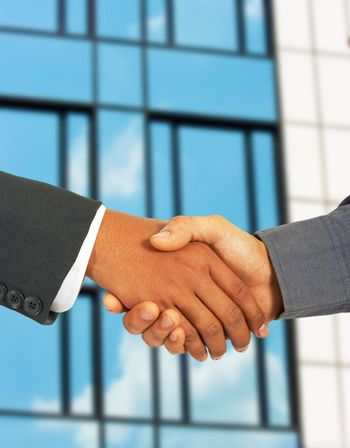 Businessmen Greet Each Other By Shaking Hands - Outside With An Office Building Background