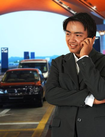 Businessman Waiting For A Taxi At The Airport And Talking On The Phone