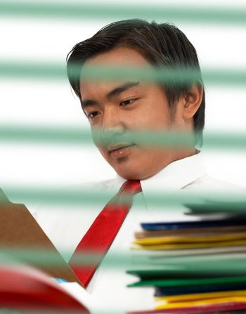 Man sitting at his office desk and reading a document in a folder
