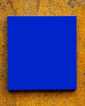 Blank blue sign on a textured wall
