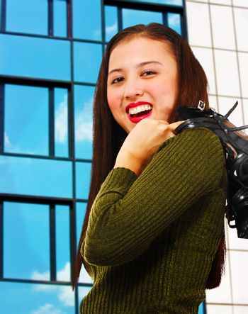 Attractive young woman smiling and standing in front of a reflective office building