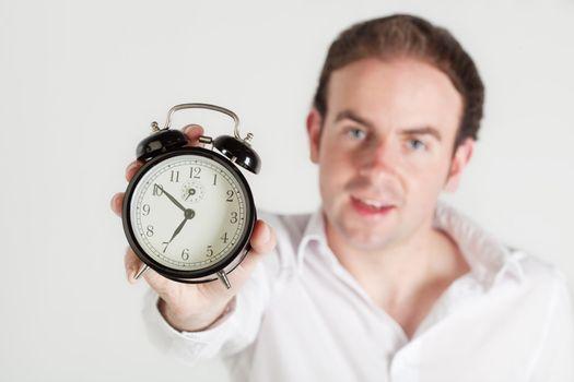Man holding alarm clock towards the camera. Clock dial in focus, man out of focus.