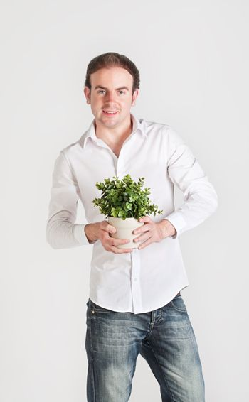 Happy young man holds a pot with decoration plant