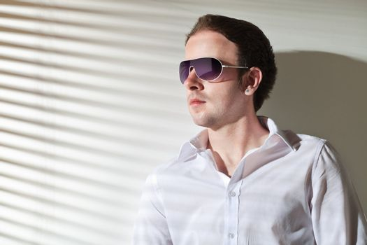 Man in sunglasses looks in the window; stripe shadows from the blinds