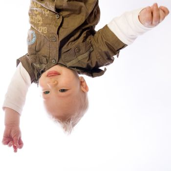 Pretty young baby boy upside down