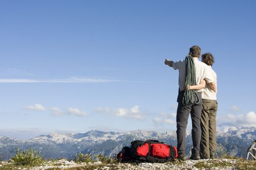 Mountaineer couple with rope and rucksacks standing on a mountain summit