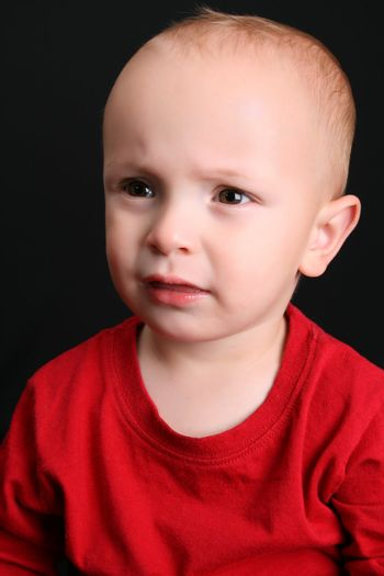 Cute toddler wearing a red shirt with a frown