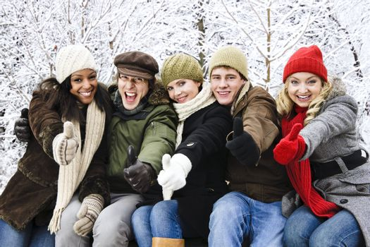Group of diverse young friends showing thumbs up outdoors in winter