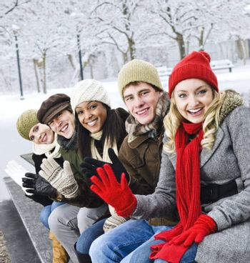 Group of diverse young friends waving hello outdoors in winter