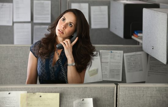 Woman office worker rolls eyes while on telephone