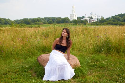 Girl Sits On flowers Field Stone
