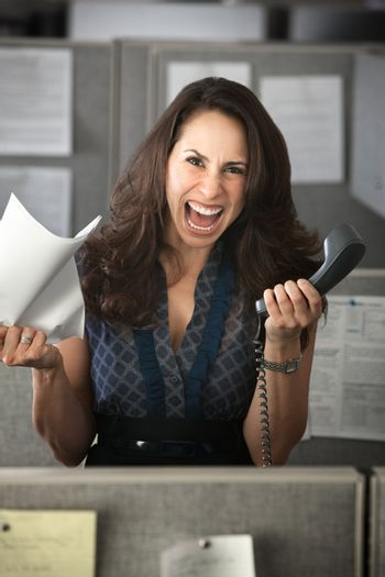 Screaming woman with phone and notes in office cubicle