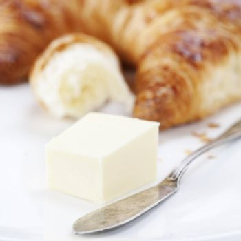 fresh croissant with butter and knife