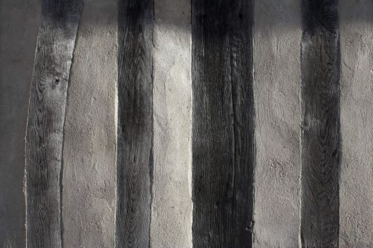 Background texture formed by a side-lit wall of an old half-timbered house in France.