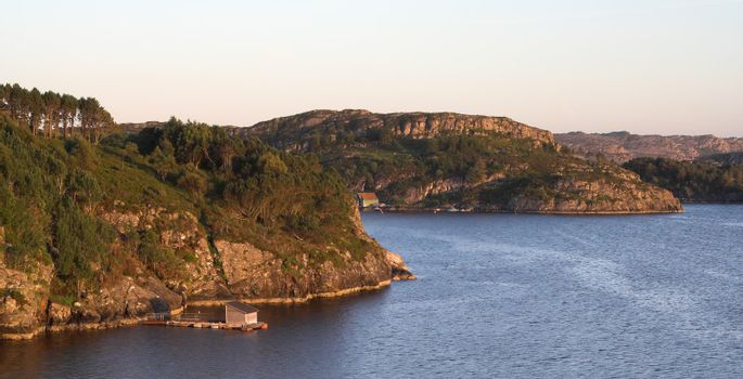 Rocky sea coast in sunset - Norwegian fjords; clear sky, still water with ripples