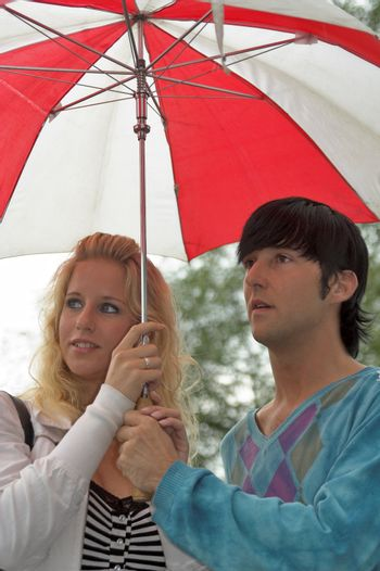 Young adult couple under umbrella