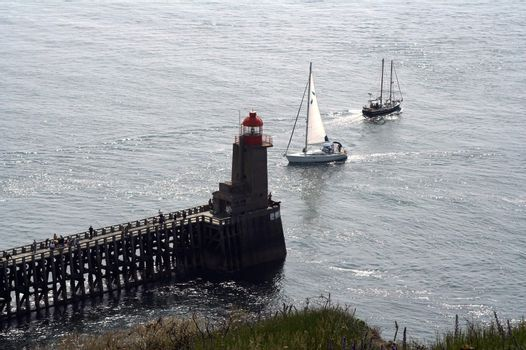 One boat coming to marine and one leaving - both are near the lighthouse built at the end of a pier. Many fishermen angling at the pier.