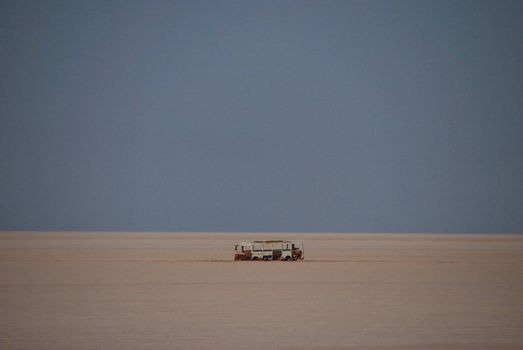 A bus is lost in the sand of the desert, far horizon