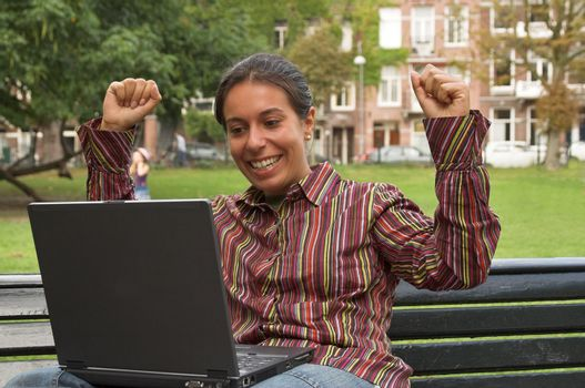 excited girl sitting on a park bench with laptop computer