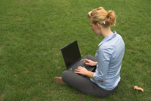 woman sitting on grass and working with laptop computer