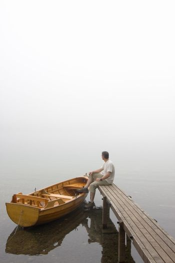 Man sitting on a landing stage at a misty morning in fall