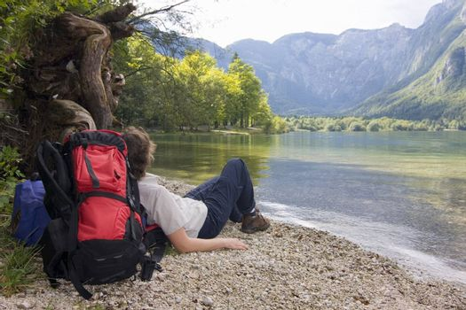 Female hiker with rucksack resting at a mountain lake