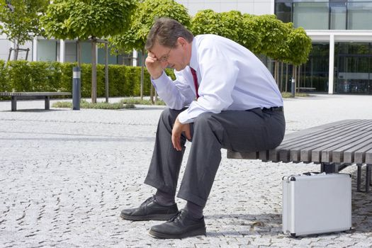 Sorrowful businessman sitting on a bench in front of an office building