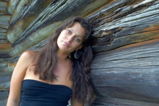 Beautiful girl near the wooden wall