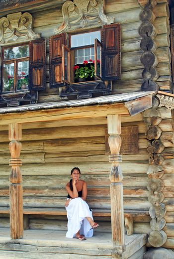 Young woman in front of Old Russian wooden house