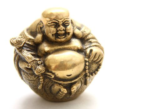 Portrait of a gold laughing buddha statuette.