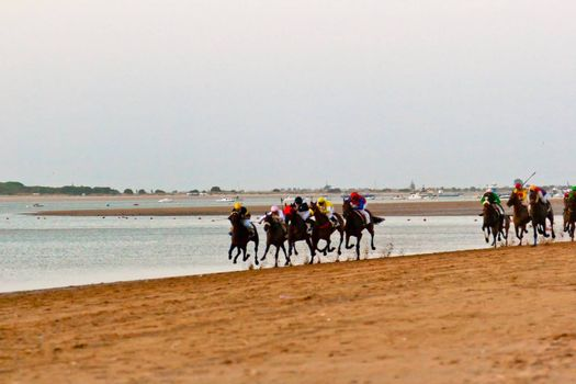 SANLUCAR DE BARRAMEDA, CADIZ, SPAIN - AUGUST 10: Unidentified riders at the start of race horses on Sanlucar de Barrameda beach on August 10, 2011 in Sanlucar de Barrameda, Cadiz, Spain.
